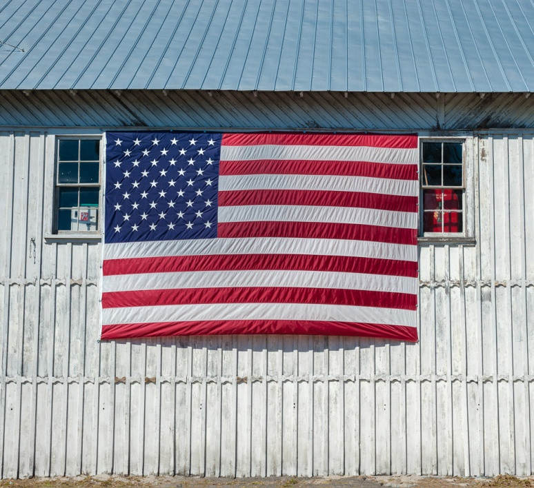 Large U.S. Flag on the side of a building.