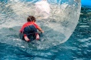 Young boy in a pool inside of a floating bubble