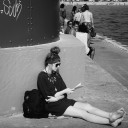 Young woman sitting on pier reading.